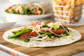 shredded barbecued chicken wraps with carrot, cheese, avocado an