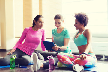 group of happy women with tablet pc in gym