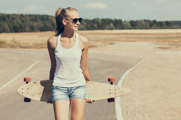 Beautiful and fashion young woman posing with a longboard