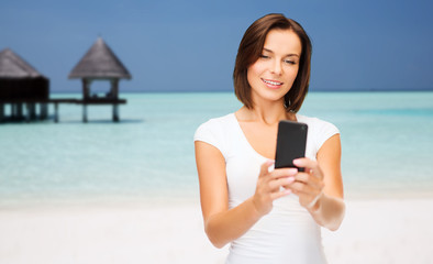 happy woman taking selfie by smartphone over beach