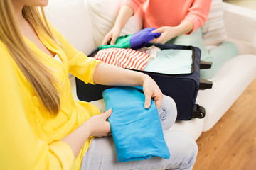 young woman packing clothes into travel bag