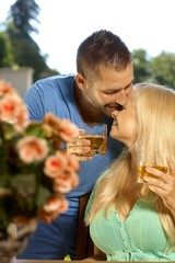 Romantic young couple with drinks kissing
