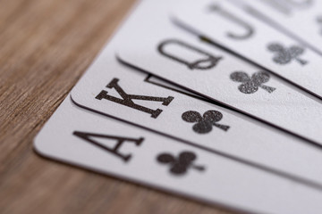 Set of Clubs suit playing cards on wooden desk