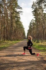 Joggerin macht Dehn und Stretchübungen in freier Natur