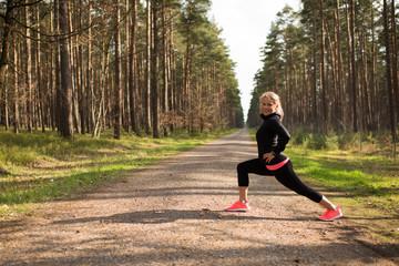 Joggerin macht Dehnübungen auf einem Schotterweg im Wald