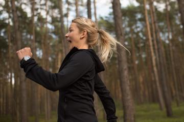 Joggerin läuft voller Freude und Elan im Wald herum