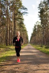 Sportliche blonde Frau walkt auf einem Schotterweg im Wald