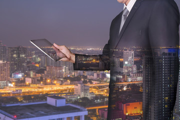 Double exposure of businessman looking the tablet and street city night