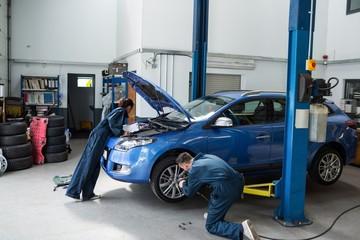 Mechanics examining a car engine and fixing wheel