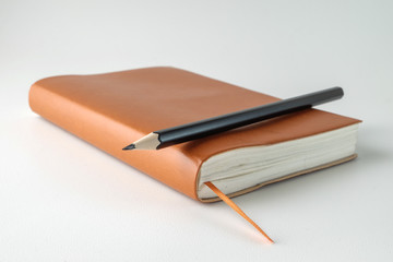 top view blank orange leather diary and pencil on white desk