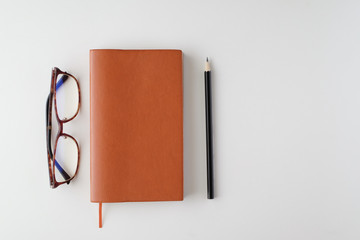 top view blank orange leather diary, pencil and glasses on white desk