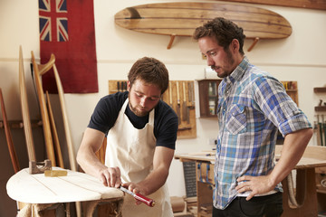 Carpenter With Apprentice Making Bespoke Wooden Surfboard