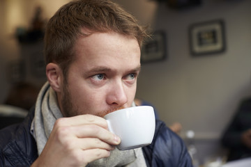 Close up of young man drinking coffee in cafe