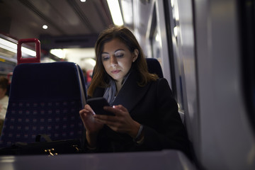Woman Sitting In Train Carriage Sending Text Message