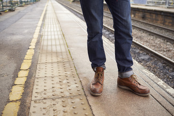 Detail Of Man Standing On Railway Platform Waiting For Train