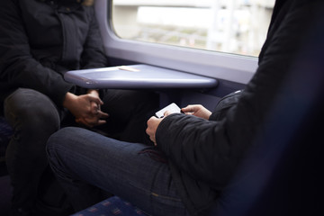 Man Sitting In Train Carriage Looking At Text Message