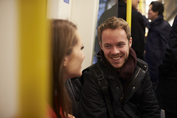 Young Couple Sitting In Train Carriage On Railway Journey