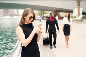 Business woman typing message while business couple walking in background.