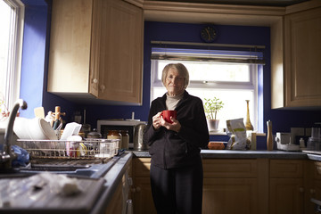 Portrait Of Senior Woman With Hot Drink In Kitchen