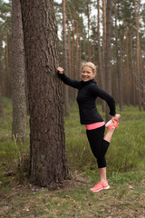 Joggerin macht Dehnübungen an einem Baum im Wald und lacht