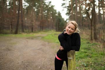 Zufriedene Joggerin stützt sich im Wald auf einen Holzpfeiler