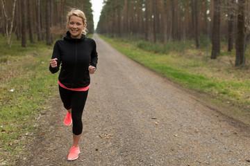 Sportliche junge Frau joggt auf einem Schotterweg im Wald
