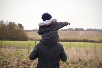 Father Gives Son Ride On Shoulders During Countryside Walk