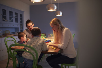 Family Sitting At Kitchen Table And Painting Picture
