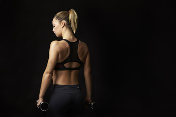 Blonde woman in sports clothing holding dumbbells, back view
