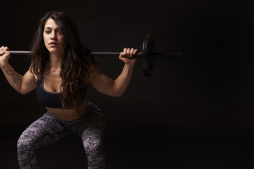 Muscular dark haired woman in half squat with barbell