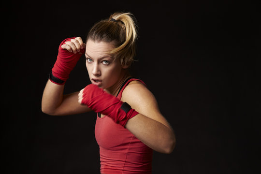 Young blonde woman shadow boxing, in a blocking position