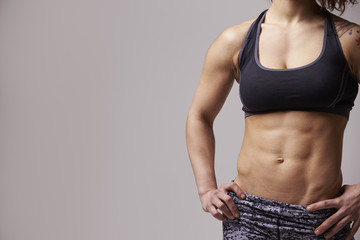 Crop shot of muscular woman with hands on hips