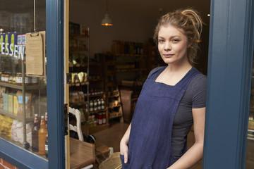 Portrait of female owner standing in shop door