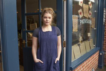 Portrait of female  owner standing in shop door