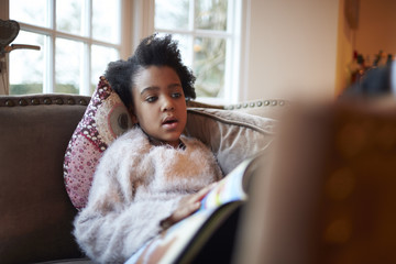 Girl reading book on sofa at home
