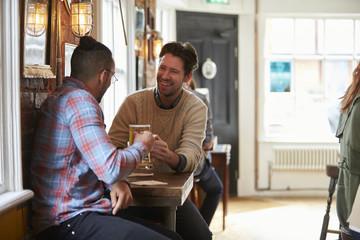Two Male Friends Enjoying Drink In Bar
