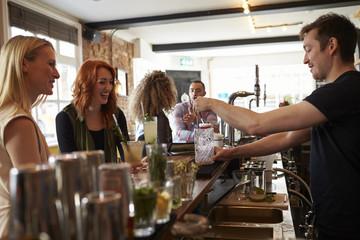 Female Friends Enjoying Drink In Cocktail Bar