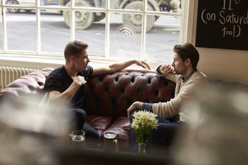 Friends enjoying drink while sitting in bar