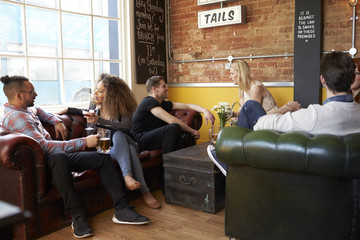 Friends enjoying beer while sitting on a sofa in a bar