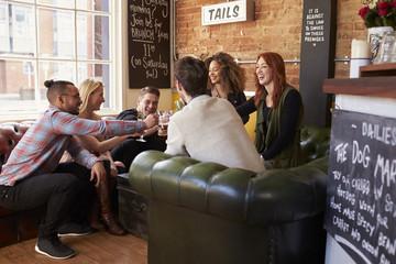 Group Of Friends Enjoying Drink In Bar Sitting On Sofa