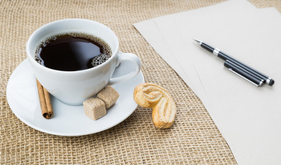 Cup of coffee, cookie, pen and paper on sackcloth background