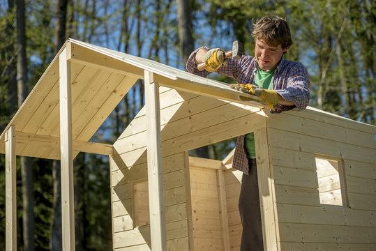 Young man using a mallet to fix a nail into a roof of a wooden p