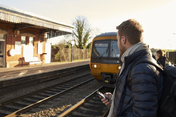 Man Standing On Railway Platform Waiting For Train To Arrive