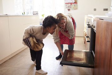 Mother And Daughter Checking Cupcakes Into Oven