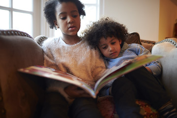 Brother And Sister Reading Book On Sofa Together