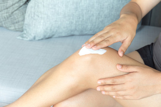 Young woman applying legs cream