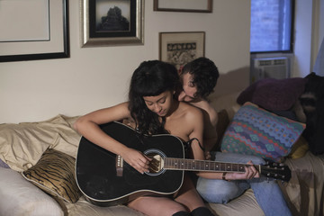 Young couple playing guitar together