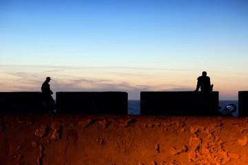 Silhouettes of unidentified tourists in Essaouira Fortress at sunset, Morocco