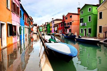 Colorful houses lined along the canal at Burano island, Venice, reflecting in wet street pavement