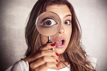 Astonished girl using magnifying glass